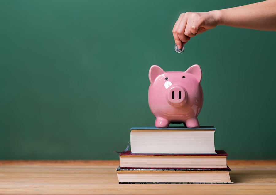 Person depositing money in a pink piggy bank on top of books with chalkboard in the background as concept image of the costs of education ** Note: Soft Focus at 100%, best at smaller sizes
